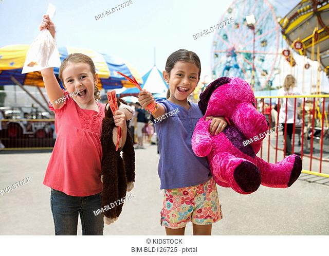 Enthusiastic girls cheering with candy at amusement park