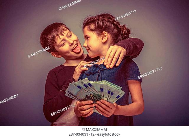 teen girl about seven years old holding a money boy teen hugging her shows tongue on a gray background, notes, fun, tease retro