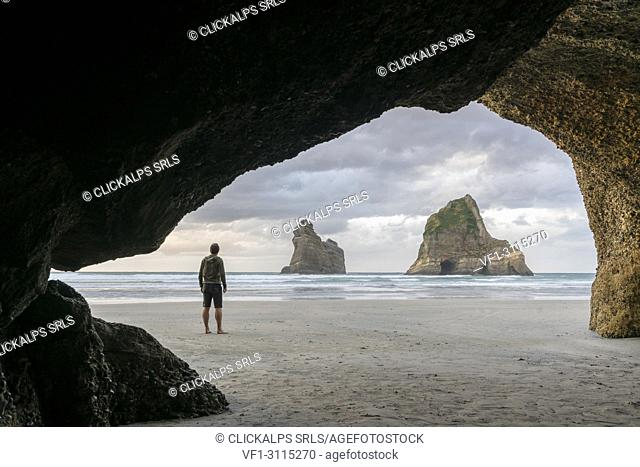 Man staring at two of the Archway Islands. Wharariki beach, Puponga, Tasman district, South Island, New Zealand