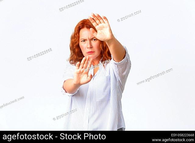 Serious-looking concerned and displeased redhead middle-aged woman protecting herself, extend hands in refusal or prohibition gesture, defending from light