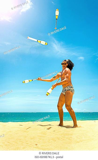 Man juggling on beach, Rio de Janeiro, Brazil