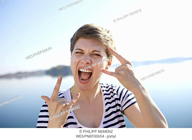 Portrait of screaming woman in front of lake showing Rock And Roll Sign