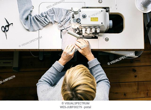 Top view of woman using sewing machine