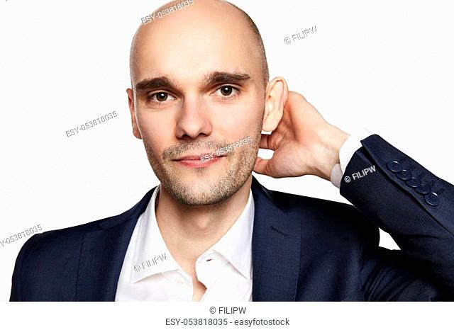 Close-up portrait of a handsome bald man stroking his head. He is smiling. White background. Horizontal
