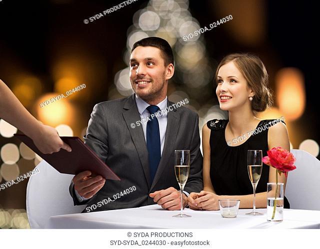 couple taking menu at christmas restaurant