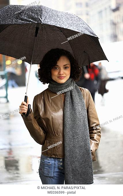 20's sexy latino/african american woman looking in camera holding umbrella in rain