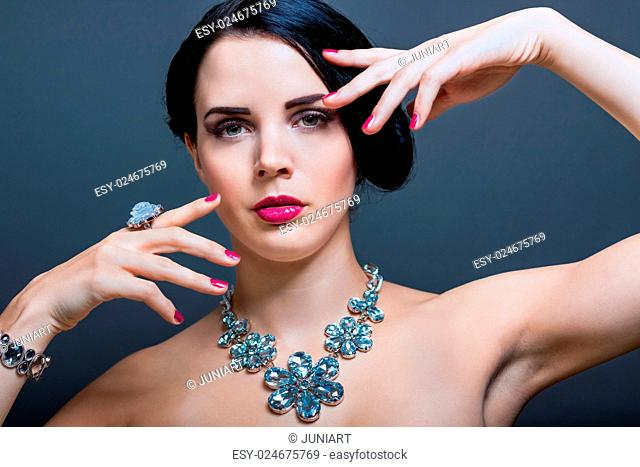 Beautiful sophisticated dark haired woman wearing elegant showy gemstone jewellery posing with bare shoulders and her hand raised gracefully to her downcast...