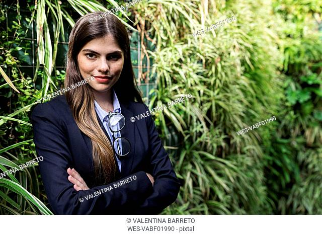 Portrait of confident young businesswoman surrounded by plants
