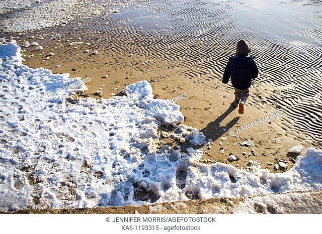 A young boy runs onto a snowy beach