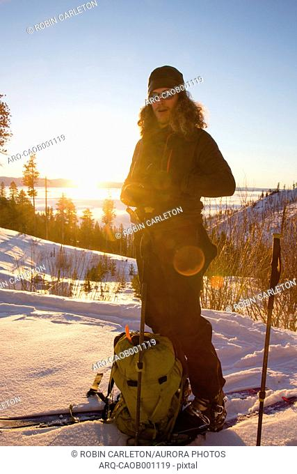 Portrait of backcountry skier with backpack taking break at sunrise