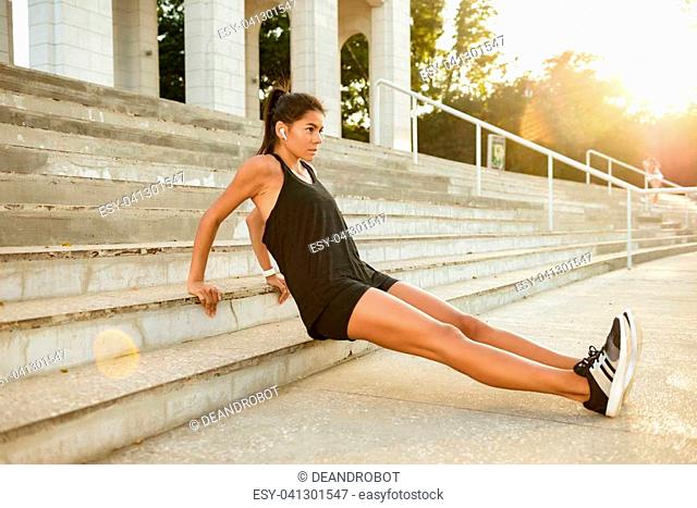 Portrait of a motivated fitness woman in earphones doing sport exercises on stairs outdoors