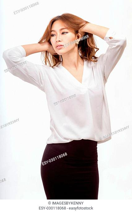 Attractive Asian American businesswoman in white blouse and black skirt with hands in hair