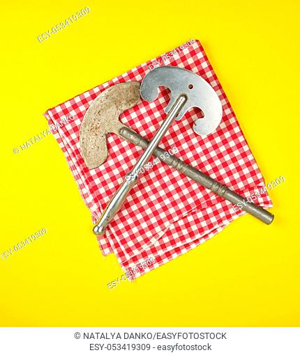 two old iron hatchets for cutting meat or vegetables on yellow background, top view