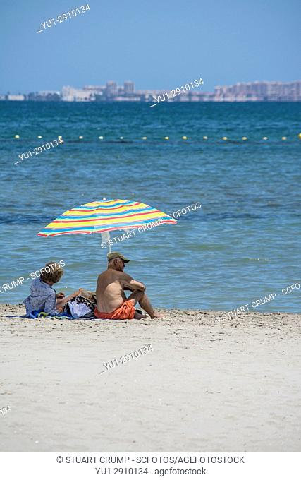 Couple under a sun umbrella on the beach by the mar menor at Los Alcazares in murcia Spain with La Manga strip in the distance