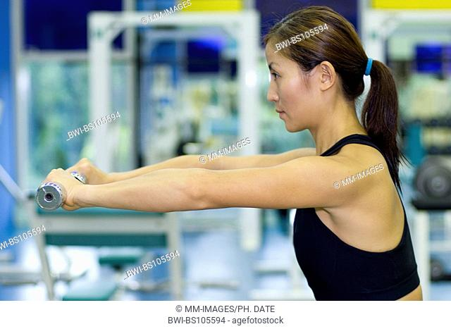 A female fitness instructor demonstrates demonstrates a dumbbell arm raise in the gym
