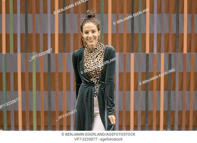 fashionable woman laughing candid in front of geometrical line pattern, in Munich, Germany