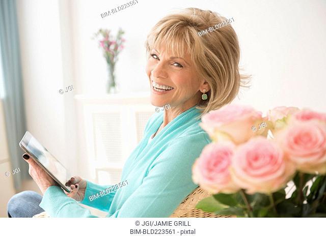 Older Caucasian woman reading digital tablet