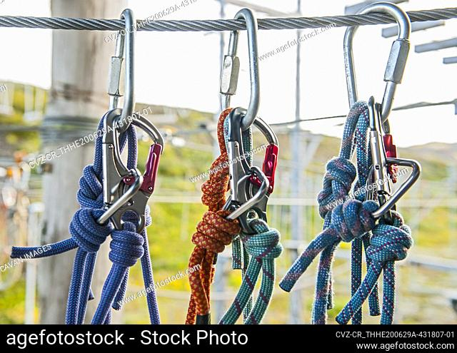 close up of carabiners on a metal wire at high rope obstacle course