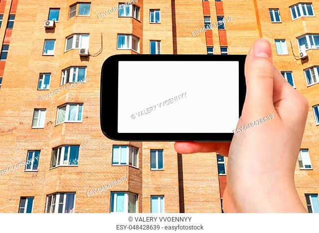 travel concept - tourist photographs of facade of urban brick multi-storey house in Moscow city on smartphone with empty cutout screen with blank place for...
