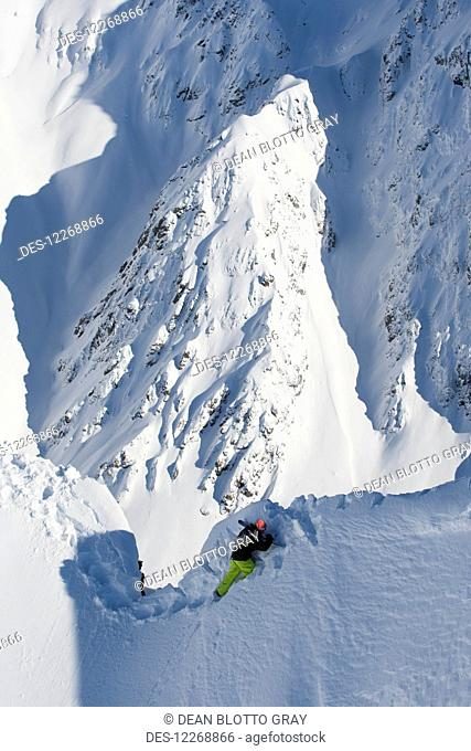 High angle view of snowboarder walking along snowy ridge; Methven, New Zealand