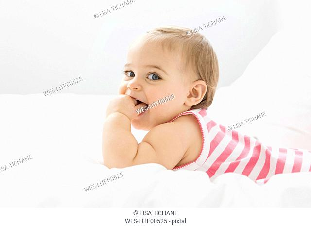 Portrait of baby girl relaxing on white bed with fingers in her mouth