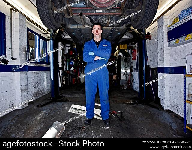 car mechanic posing under a car at automotive garage in the UK
