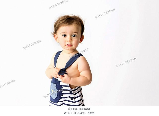 Portrait of toddler wearing striped dungarees standing in front of white background
