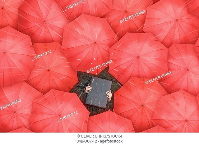 Person with briefcase over head standing between red umbrellas, directly above
