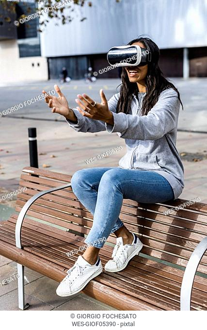 Young woman sitting on a bench, using VR goggles, reaching out with her hands