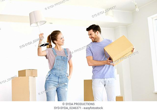 couple with boxes and lamp moving to new home