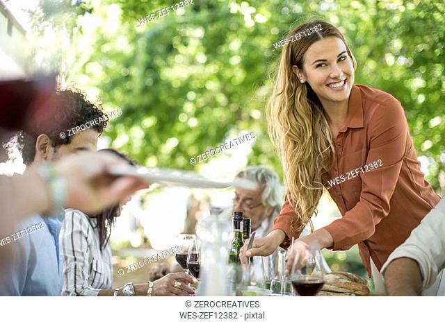 Smiling woman dishing up at family lunch in garden