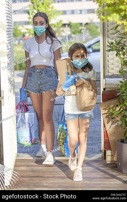 sisters wears masks and gloves and enters house with shopping