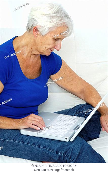 Senior woman sitting on her sofa and writing on her laptop