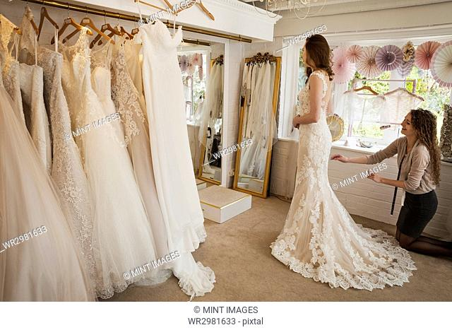 Rows of wedding dresses on display. A young woman in a full length white wedding dress, looking at her reflection in the mirror in a bridal boutique