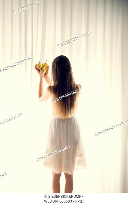 Young woman standing in front of a white curtain holding three pears in her hands, back view