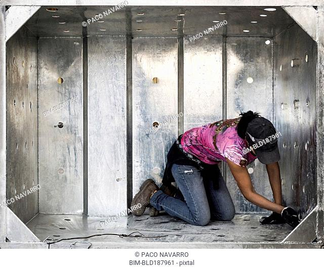Worker examining metal walls