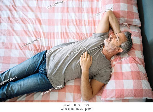 Relaxed mature man lying on bed