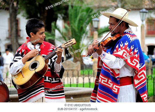 Musicians playing violin and guitar during performance of Danza de los Viejitos or Dance of the Little Old Men in Plaza Vasco de Quiroga