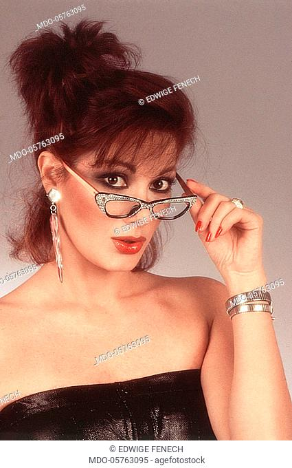 French-born Italian actress Edwige Fenech getting off a pair of eyeglasses. 1983