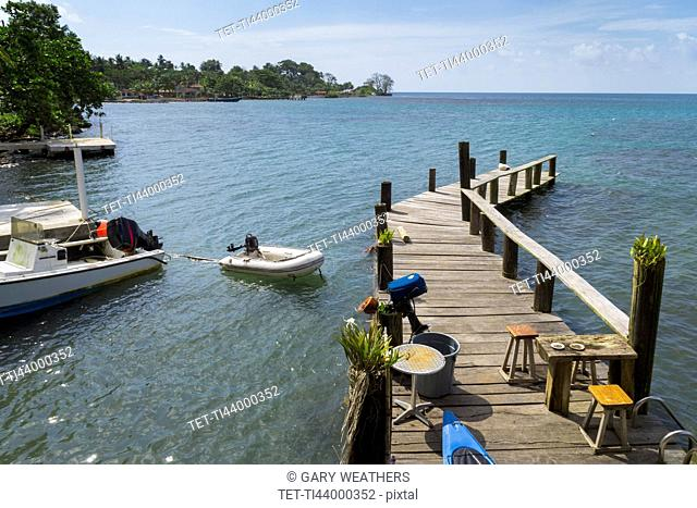 Wooden jetty with motor boat nearby on sea