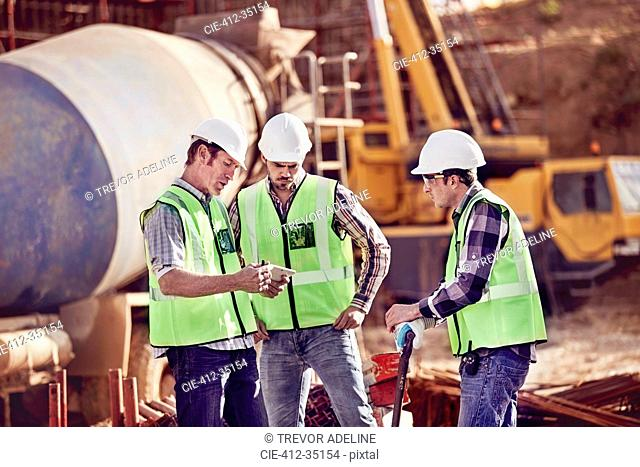 Construction workers meeting, using digital tablet at construction site