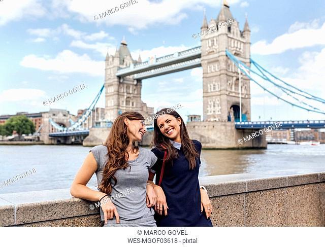 UK, London, two smiling women near the Tower Bridge