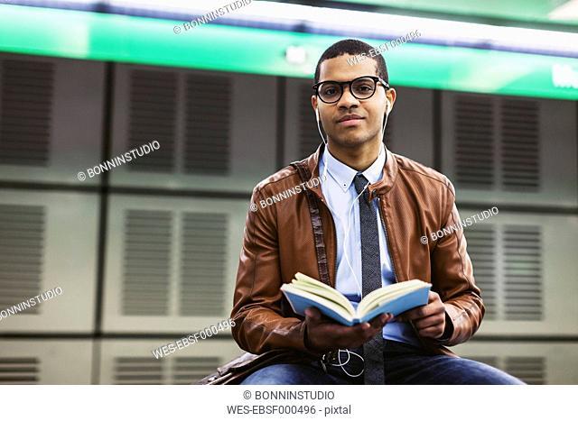 Spain, Barcelona, businessman sitting at underground station platform with book