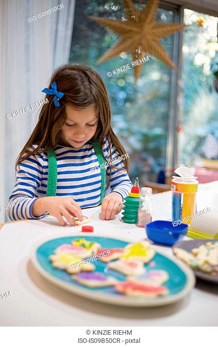 Girl decorating christmas cookies for plate on kitchen counter
