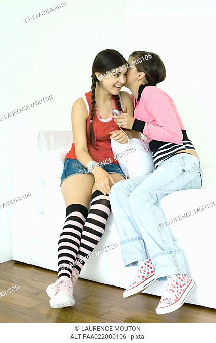 Two young female friends sitting on sofa, one whispering to the other