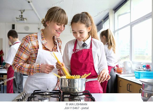 Home economics teacher teaching high school student pasta cooking