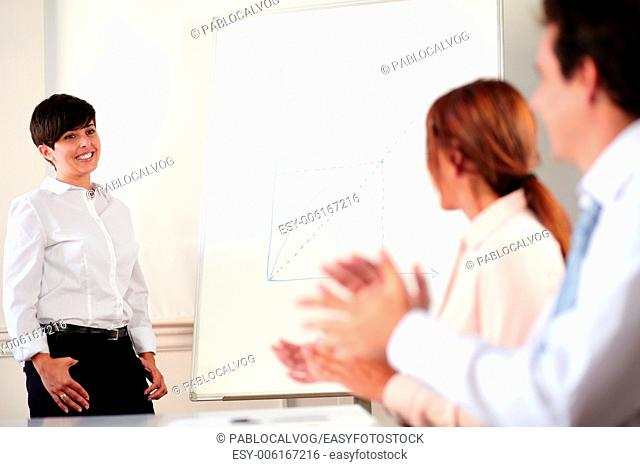 Portrait of a charming young businesswoman giving a presentation while standing in front of white board
