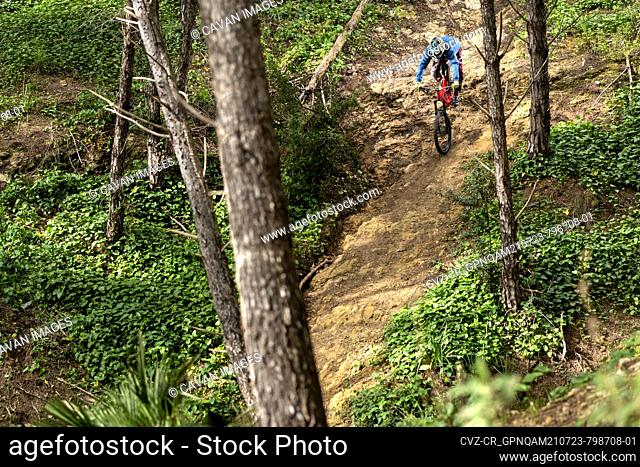 Young cyclist downhill in dangerous trail in the forest