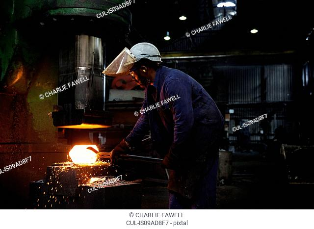 Forge worker pre forms steel billet on 5 tonne clear space hammer before it will be presented to set of two dies to be fully forged in hammer