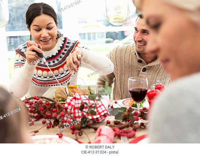 Woman cutting Christmas turkey at table